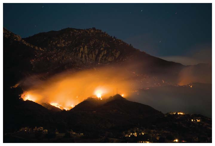 Almost 300 homes were lost during a 2008–2009 series of wildfires in the hills of the Santa Barbara region of California, including the May 2009 Jesusita wildfire, shown here burning in the foothills above Santa Barbara on its first night, ultimately incurring a cost of $20 million. As climate change alters temperature and precipitation regimes, wildfires in some regions are becoming more likely. Despite ample research informing ways to plan for fire and prevent damages, pervasive misunderstandings hinder better policy. <strong>Cody Duncan/Alamy Stock Photo</strong>